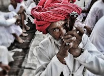 man met rode tulband en lange, witte kleding rookt een pijp in tussen zittende mensen