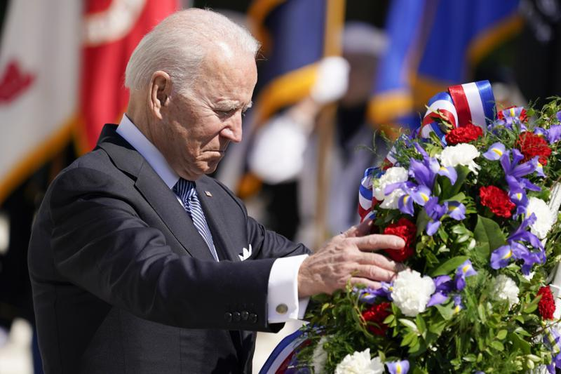 President Joe Biden adjusts a the wreath at the Tomb of the Unknown Soldier at Arlington National Cemetery on Memorial Day, Monday, May 31, 2021, in Arlington, Va.(AP Photo/Alex Brandon)