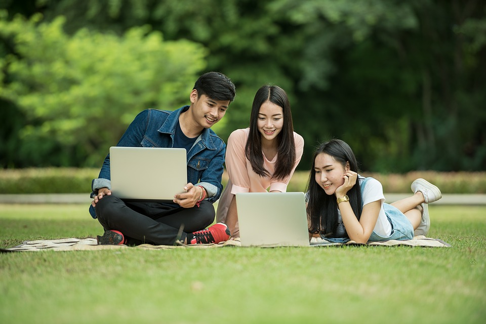 students relaxing in field with computers