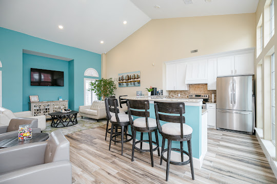 Community clubhouse with wood-inspired flooring, seating, and blue accent wall