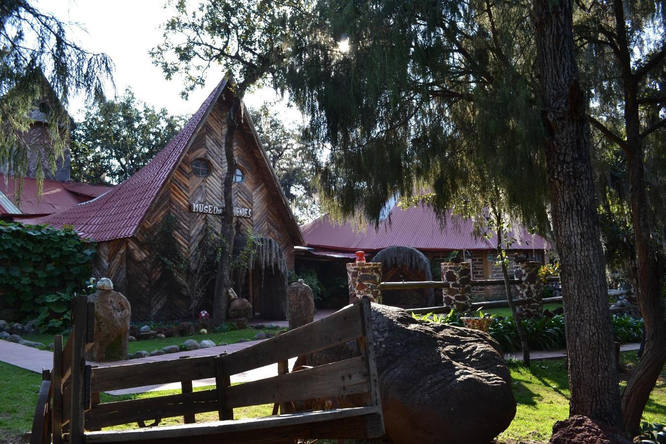 Una casa de madera en el bosque  Descripción generada automáticamente con confianza baja