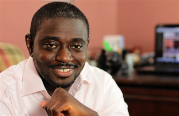 Ademola Ogundele, Nigerian influencer and founder and CEO of popular music website, NotJustOk smiling in front of desk - Top 25 Social Media Influencers Making Impacts in Nigeria Today