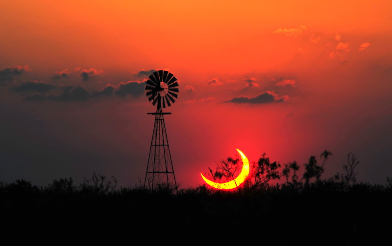 Photo: A Partial Solar Eclipse over Texas Image Credit & Copyright: Jimmy Westlake (Colorado Mountain College) & Linda Westlake http://apod.nasa.gov/apod/ap120522.html  It was a typical Texas sunset except that most of the Sun was missing. The location of the missing piece of the Sun was not a mystery -- it was behind the Moon. Sunday night's partial eclipse of the Sun by the Moon turned into one of the best photographed astronomical events in history. Gallery after online gallery is posting just one amazing eclipse image after another. Pictured above is possibly one of the more interesting posted images -- a partially eclipsed Sun setting in a reddened sky behind brush and a windmill. The image was taken Sunday night from about 20 miles west of Sundown, Texas, USA, just after the ring of fire effect was broken by the Moon moving away from the center of the Sun. Coming early next month is an astronomical event that holds promise to be even more photographed -- the last partial eclipse of the Sun by Venus until the year 2117.