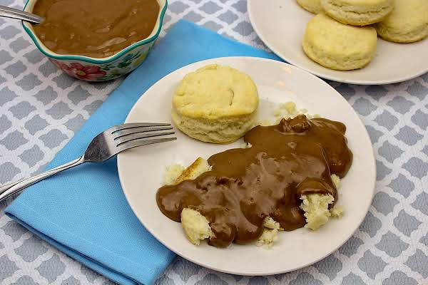 A Bowl Of Shawn's Chocolate Gravy With Some Poured Over Biscuits.