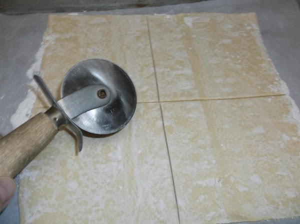 Use a pizza wheel or chef's knife to cut dough in half down the...