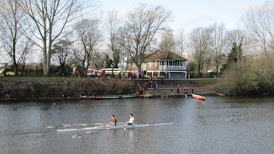 Photo: Skullers rowing down the Severn, while dragon boat crews ready their boars at the  boat club on the Severn