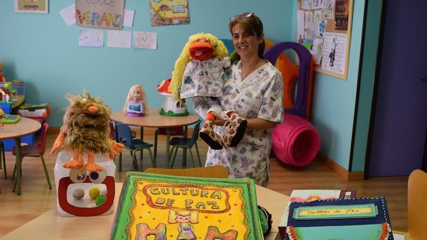 Mercedes Ortiz en el aula del Hospital  junto a la mascota de los niños 'MOM'.