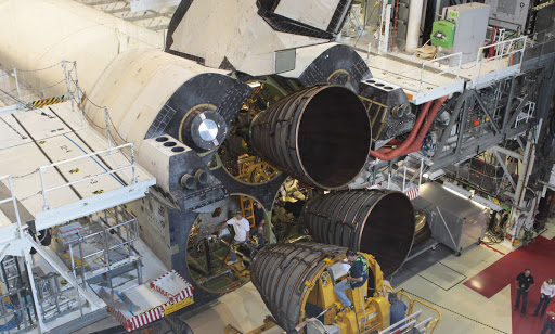 United Space Alliance technicians monitor the progress as a Hyster forklift moves replica shuttle main engine 2.