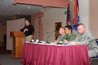 Photo: Members of the tactical issues panel, left to right:  Lt. Cmdr. Thomas Leak (at the podium), Capt. Walt Sowden, Maj. Shing Tai Leung-Singapore, Lt. Col. Joe McClamb.