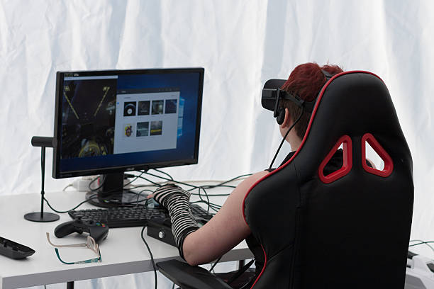 Young girl  with VR - glasses  plays game on PC  Brno, Czech Republic - April 30, 2016: Young girl with VR - glasses sits on gaming chair and plays game on PC at Animefest, anime convention on April 30, 2016 Brno, Czech Republic gaming chair stock pictures, royalty-free photos & images