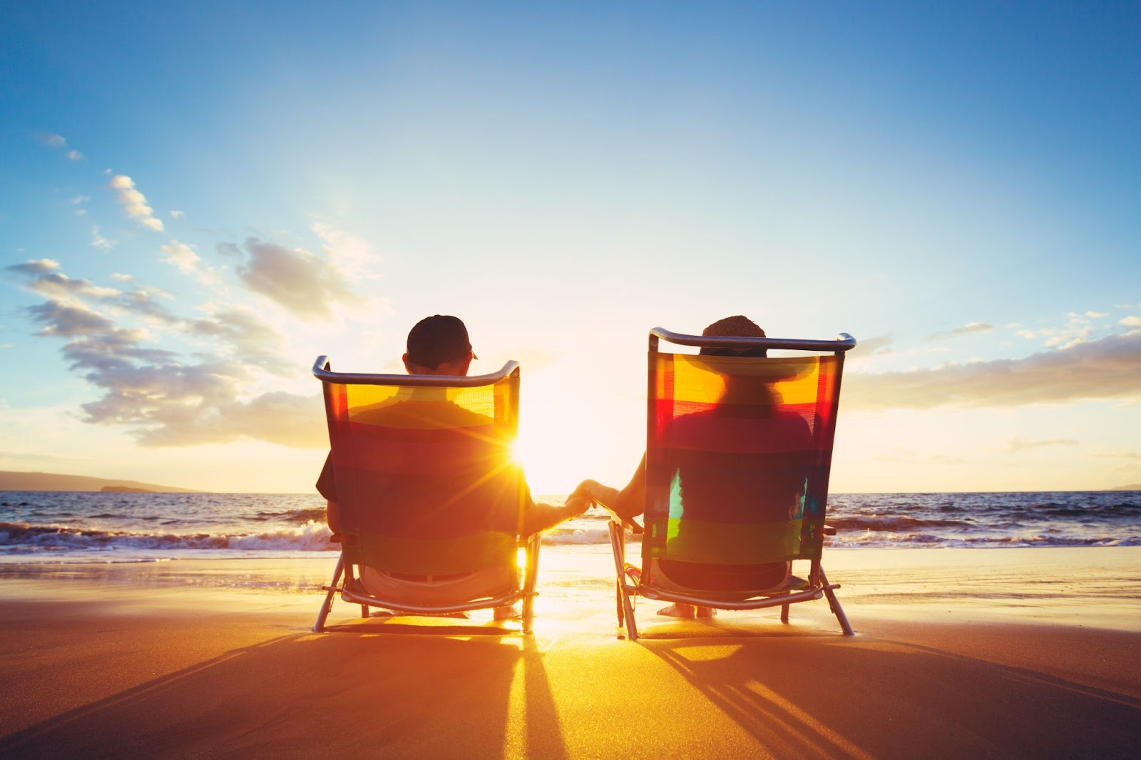 Couple holding hands while sitting on beach chairs and watching the sunset