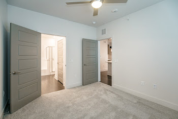 A3 bedroom with neutral carpet and ceiling fan