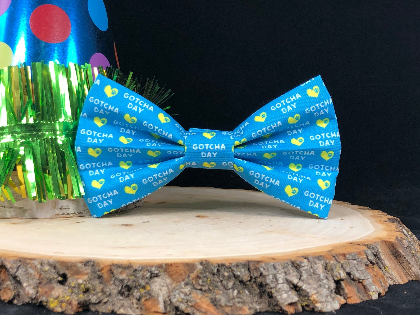 """A blue bowtie with yellow hearts that says """"Gotcha Day"""" in white"""