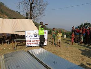 Photo: Afectados por el terremoto esperan recoger láminas de metal para sus cabañas en la aldea de Khalte, distrito de Dhading.