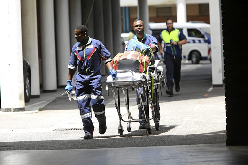 Medics leave the scene of a shooting in the Durban regional court where two people were killed in a divorce case. /JACKIE CLAUSEN