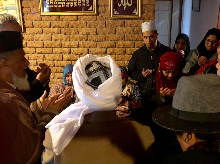 Zainab Bassa (red scarf) wife of Malmesbury mosque victim Ismail Bassa, 74, during prayers at her home on June 14 2018.