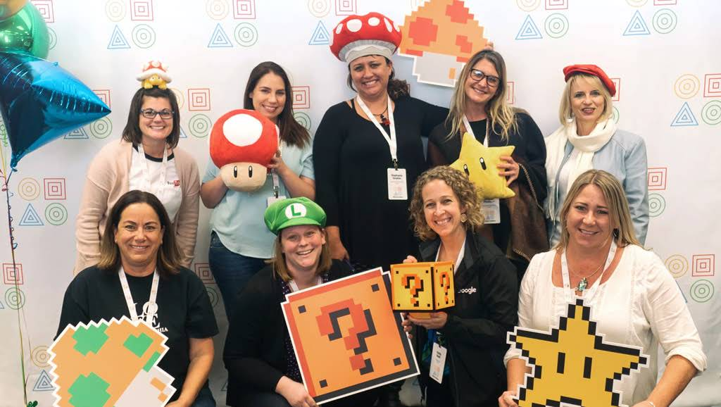 A group of educators pose for a photo wearing Super Mario Brothers hats and gear.