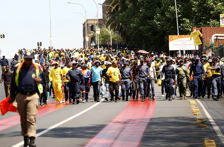 Police officers lead a group of ANC members from greater Johannesburg who marched to the offices of Mayor Herman Mashaba and Eskom to handover a memorandum demanding service delivery.