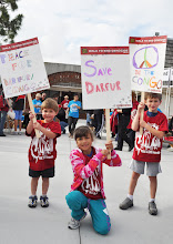 Photo: Three kids pose for the camera holding their signs.