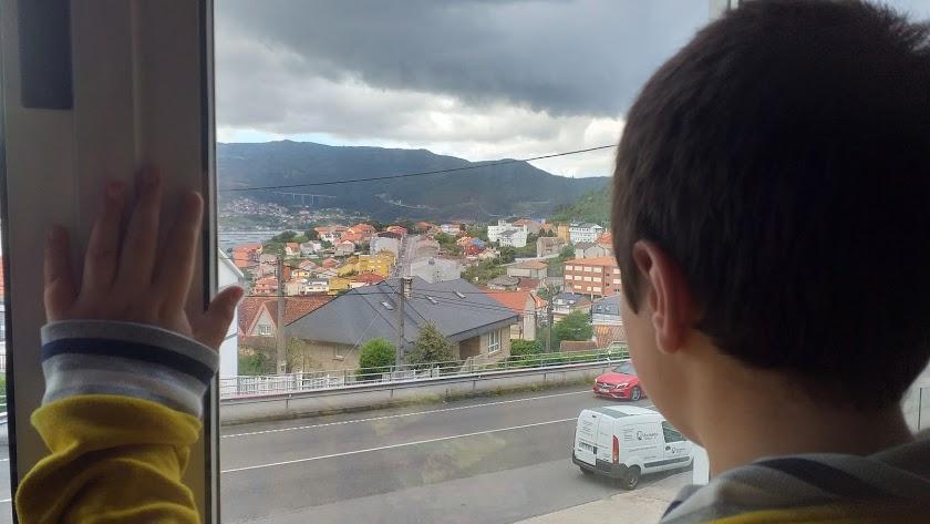 Un niño observa desde la ventana mientras se encuentra confinado.