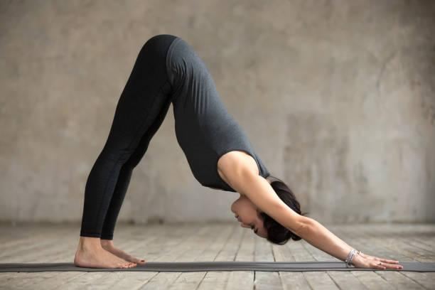 Young woman doing Downward facing dog exercise Young woman practicing yoga, doing Downward facing dog exercise, adho mukha svanasana pose, working out, wearing sportswear, black pants and top, indoor full length, gray wall in yoga studio downward dog stock pictures, royalty-free photos & images