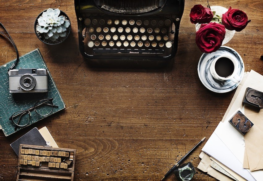 typewriter notebook pen coffee flowers writing desk image for feature image for writing tips for novice writers article
