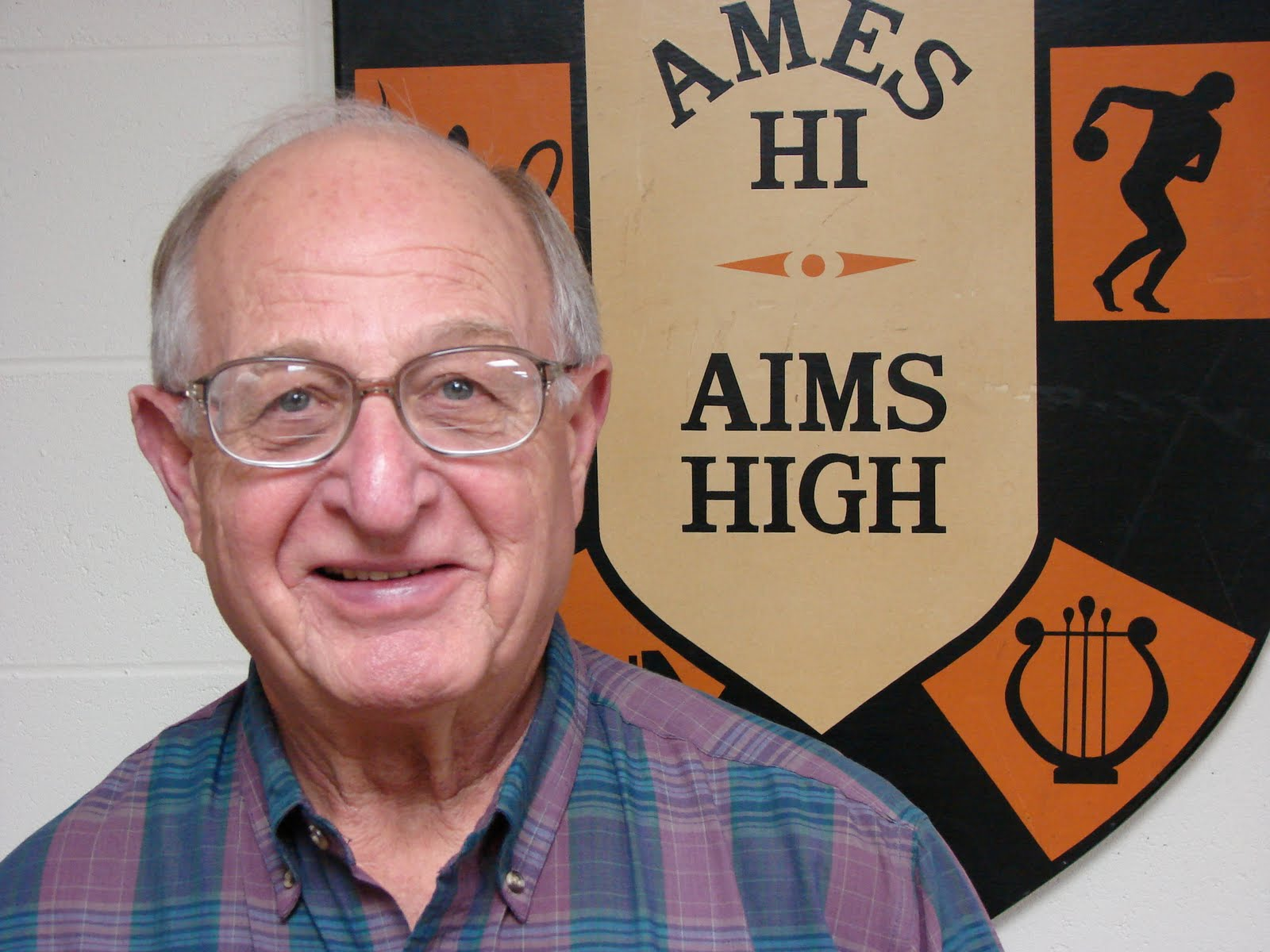 Photo: good of Bill Ripp with the Ames Hi Aims High logo behind him