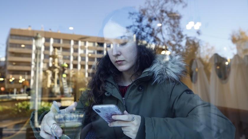 Una joven consulta su móvil en una cafetería de Granada.