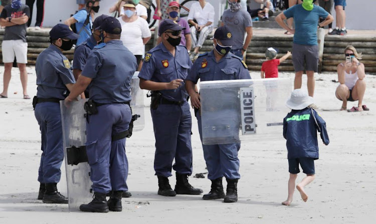 A child runs rings around public order cops' attempts to enforce the lockdown beach ban in Muizenberg on January 30 2021.