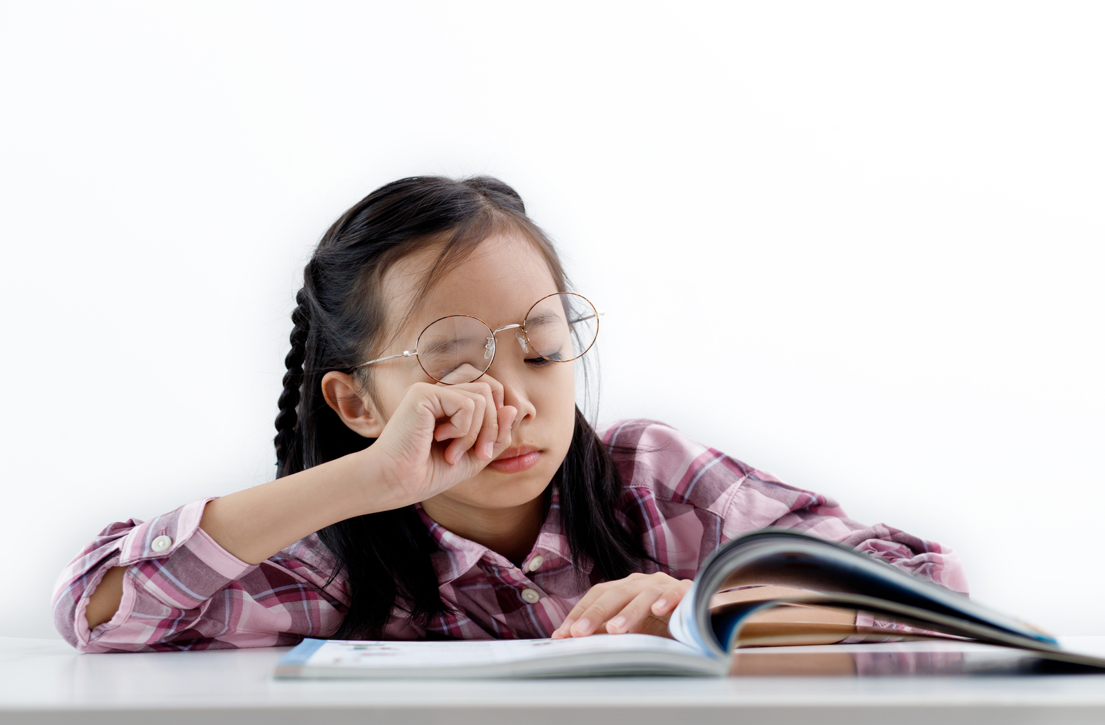 young girl reading and rubbing her dry eyes