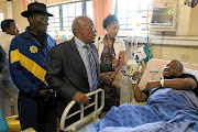 Police minister Bheki Cele, health minister Aaron Motsoaledi talk to  Dr Lucky Kunene  who survived an attack at Letaba Hospital. /Antonio MuchAvE