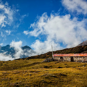 The Stone Hut by Mrigankamouli Bhattacharjee - Landscapes Cloud Formations ( clouds, sky, grass, hut, blue, meadow, stone )