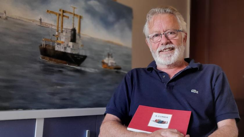 Juan Deus, gallego afincado en Almería, con su libro y junto a la imagen de un barco, un motivo siempre presente en su vida.