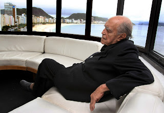 Photo: Brazilian architect Oscar Niemeyer poses at the balcony of his studio with Copacabana beach on the background 14 December 2007 in Rio de Janeiro, Brazil. Niemeyer will celebrate his 100th anniversary next 15 December.    AFP PHOTO/ANTONIO SCORZA (Photo credit should read ANTONIO SCORZA/AFP/Getty Images)