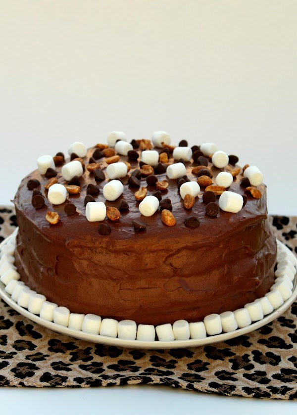 Arrange marshmallows, peanuts and chocolate on top of the cake.