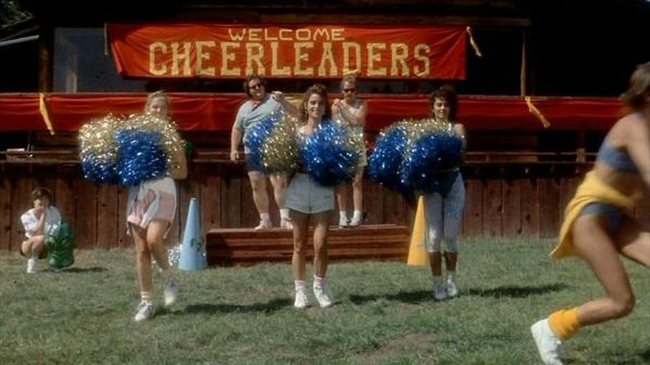 """Still from Cheerleader Camp (1989). A small group of cheerleaders dance with sparkly blue and gold pom poms, in front of a small stage and a banner saying """"Welcome Cheerleaders""""."""