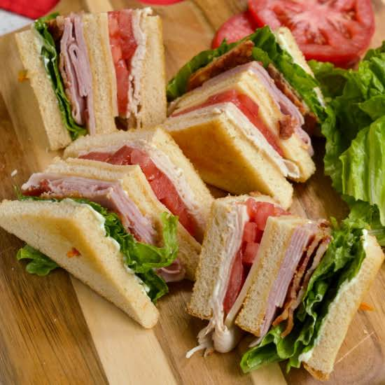 A Classic Mouthwatering Good Triple Decker Club Sandwich With Three Slices Of White Bread Toasted, Mayonnaise, Turkey, Tomato, Cheddar Cheese, Ham, Crispy Bacon, And Lettuce.