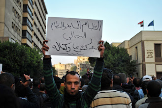 Photo: A man holding up a sign condemning SCAF.