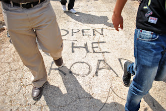 Photo: The graffiti reading 'Open the road' referes to a blocked roadway reserved exclusively for Jewish settlers in the West Bank village of Kufr Qaddoum.