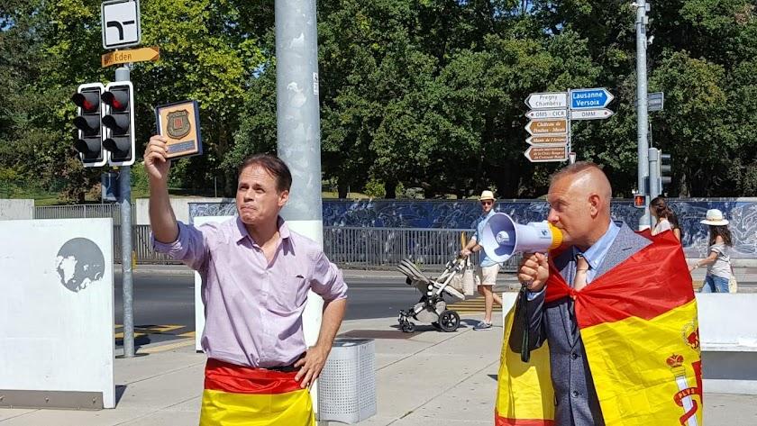 Meylan (izquierda) muestra una placa de los Mossos en una concentración a favor de la unidad de España en una plaza de Ginebra.