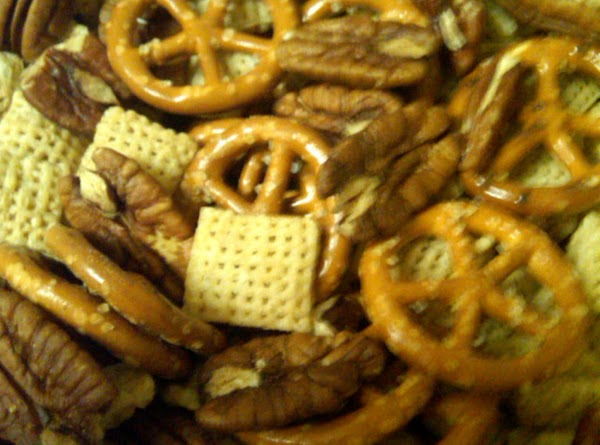 In a large microwave-safe bowl, mix together the Rice Chex, pretzels, and nuts.