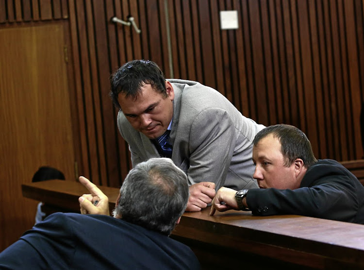 Willem Oosthuizen and Theo Jackson talk to their lawyer in the Middelburg Magistrate's Court. File photo.
