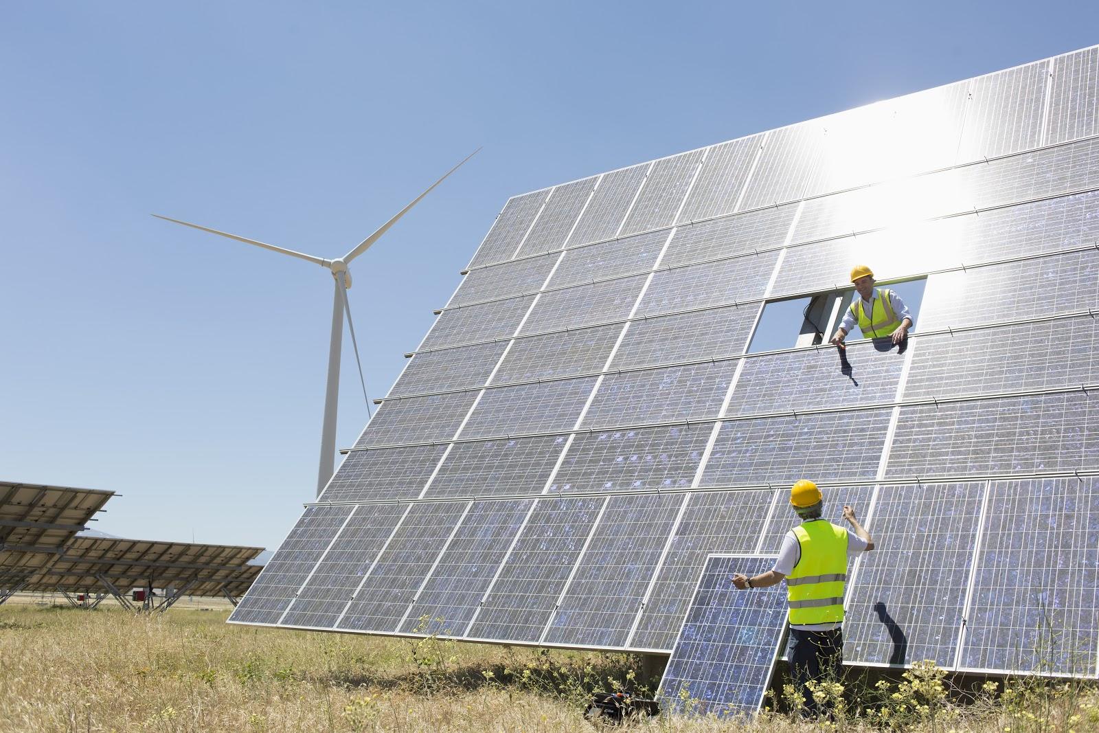 Imagem de placas fotovoltaicas de energia solar em manutenção. Há a presença de dois homens, uniformizados e trajando EPIs.