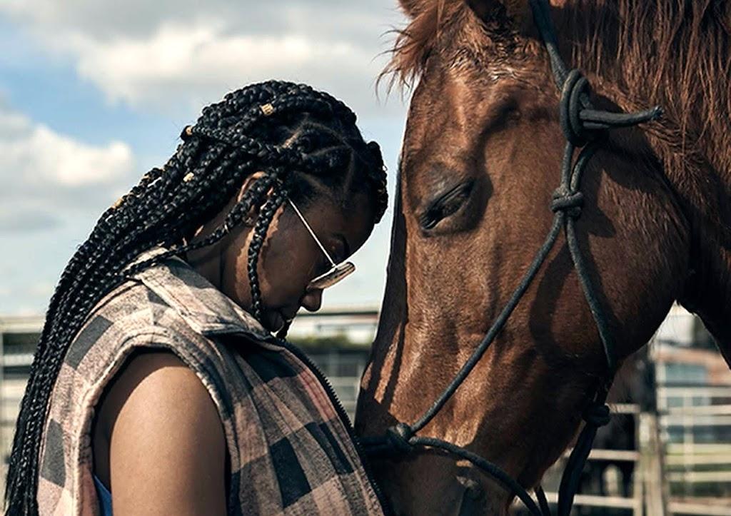 Una mujer negra de pie frente a su caballo disfruta un momento de paz.
