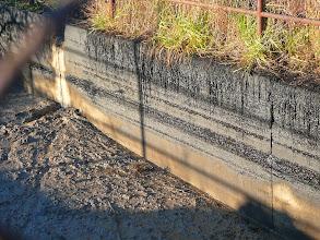 Photo: 12.1.2014 - Z usazenin na stěnách jímky (která není opatřena taktéž žádnou izolací) je patrná kontaminace tekutiny ze skládky ropnými látkami. — Dekontaminační plocha Rokytí.