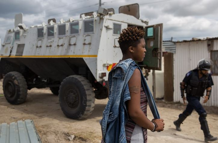 A resident watches as shacks are demolished by the Anti-land Invasion Unit in Makhaza, Khayelitsha.