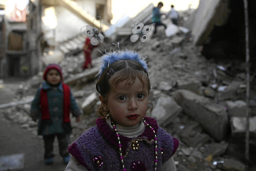 Under siege: A girl poses for a picture near damaged buildings in the rebel-held besieged city of Douma, northeast of the Damascus suburb of Ghouta, Syria, last week. Picture: REUTERS