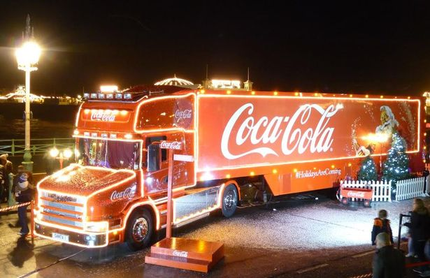 Bright Christmas Coca-Cola truck with lights wrapping around it and an image of Santa Claus on the truck.
