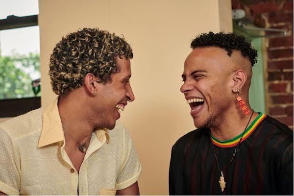 Two Latinx men laugh together in a light-filled cafe