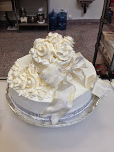 Photo: Smooth white iced wedding cake w/ivory frosting roses, ivory French ribbon bow wrapped around top tier & silver diamond wrap trim.